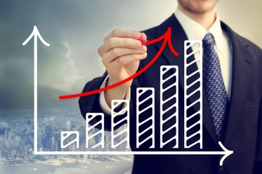 Businessman drawing a rising arrow over a bar graph above the city stock vector