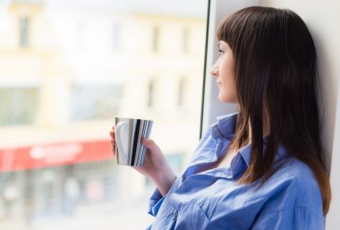 Woman with a cup of tea looking through the window