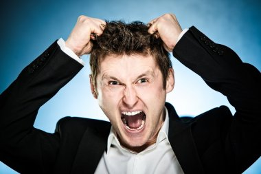 Angry businessman pulls his hair out