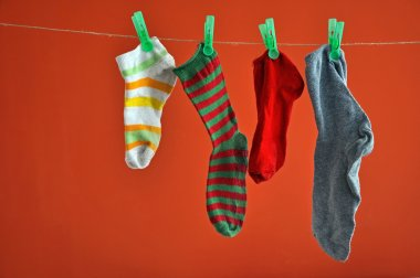 Different types of striped socks hanging on a rope isolated on red