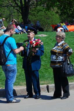 A war veteran receives flowers from a young man.