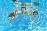 Fotografie Happy smiling family underwater in swimming pool