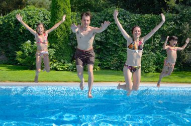 Happy family with kids jumping to swimming pool