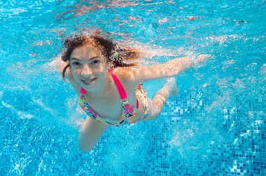 Happy underwater girl swims in pool