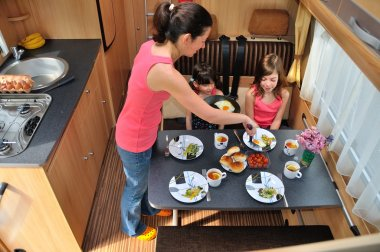 Family eating together in RV (camper) interior