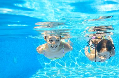 Happy girls swim underwater in pool