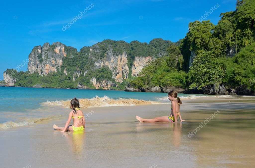 Happy girls play in sea on tropical beach