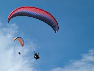 Paragliding against clear blue sky
