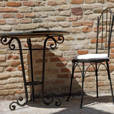 Wrought iron chair and table on sunny terrace