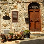 Vstup do toskánské vily s mnoha květináče na ulici