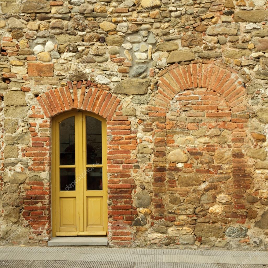 old brick and stone wall with door to the tuscan house