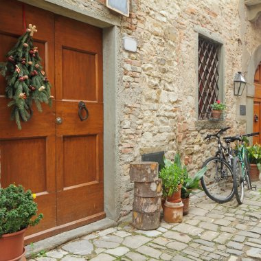 Doorway to the tuscan house with christmas wreath and parked bicycles