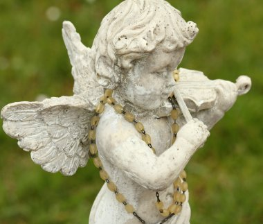statue of little angel playing violin