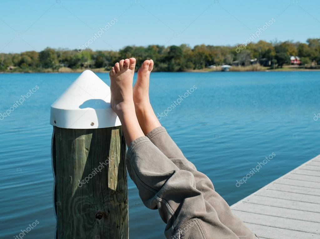 Child's bare feet hanging off pier on a lake or river