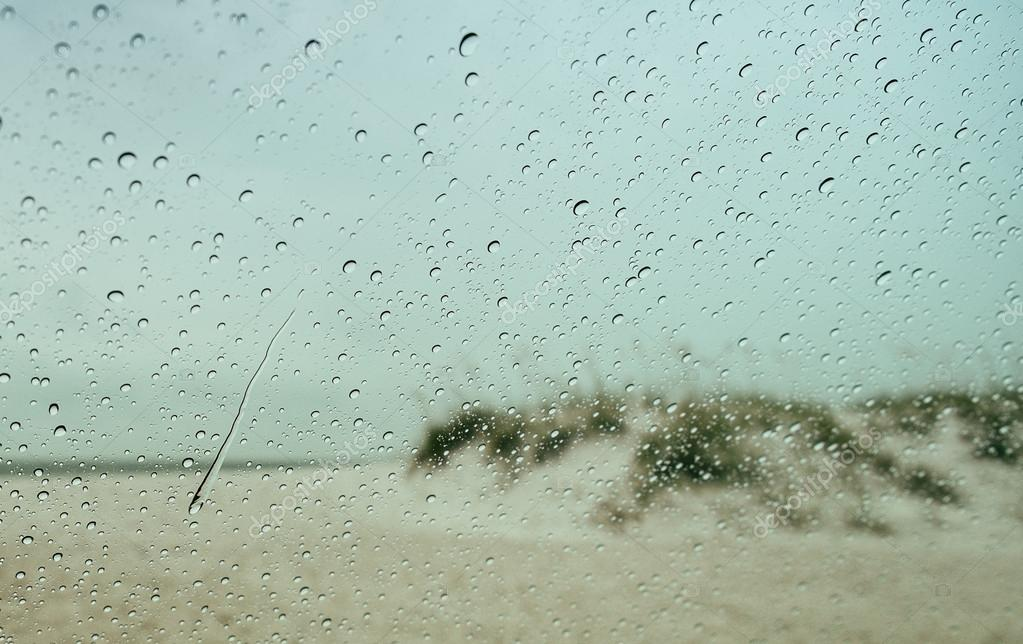 Rain and Raindrops on Car Windshield Looking Out at Beach