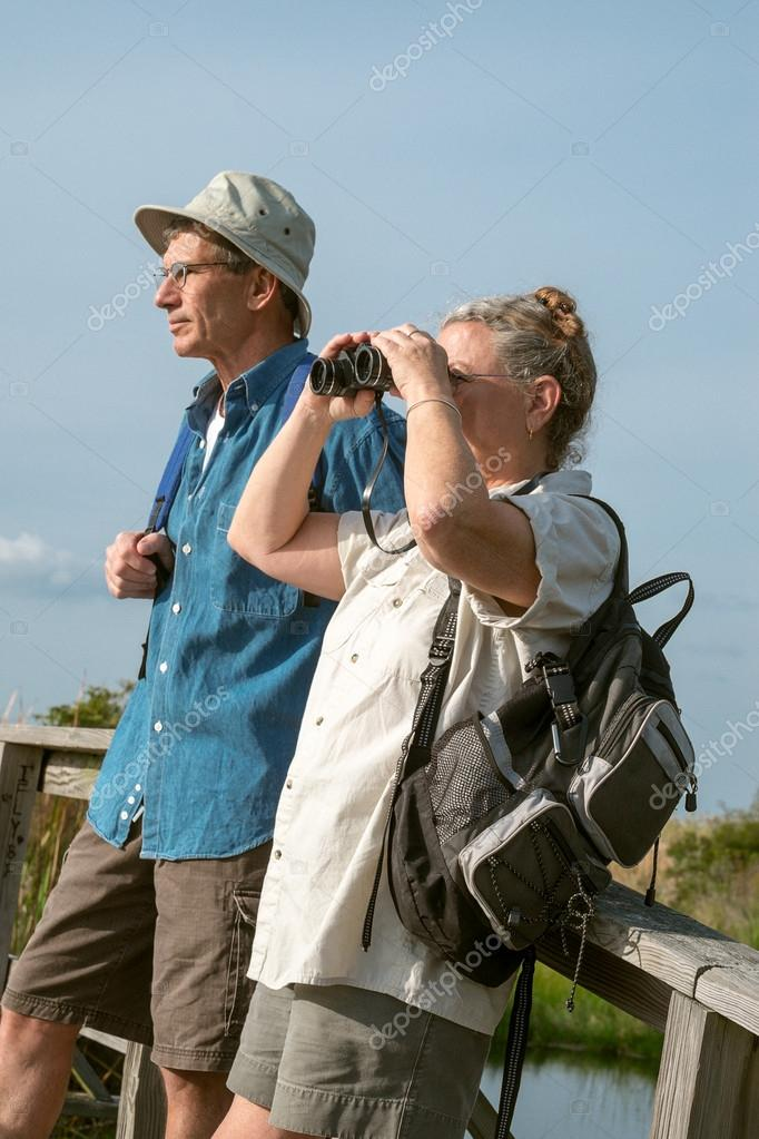 Senior Couple Hiking and Birdwatching with Binoculars