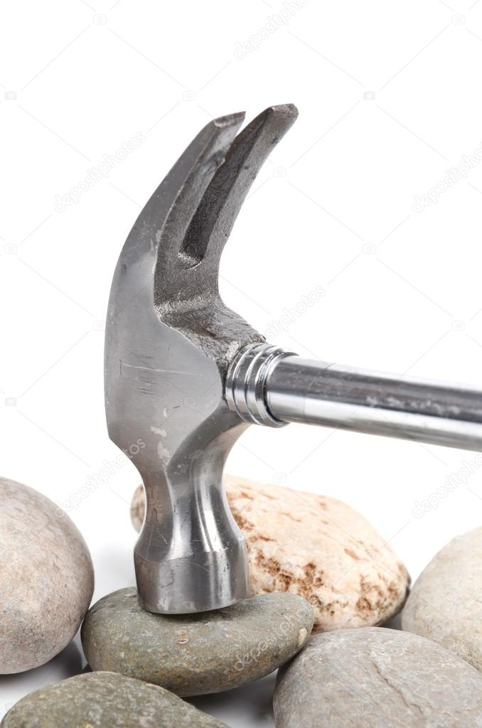Hammer and stone on white background