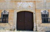 Fotografie altes Haus mit Wappen über dem hölzernen Tor