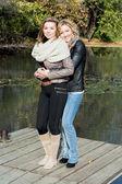 Dvě krásné mladé ženy a rybník v podzimním parku
