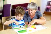 šťastná babička dělá domácí práce s vnukem