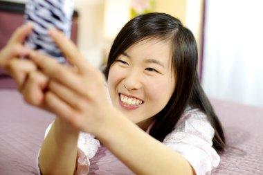 Cute asian american woman in bed taking selfie smiling