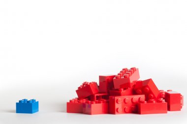 A large group of red lego blocks and one blue block