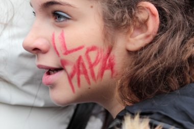 Young italian faithful with 'The Pope' written on the cheek