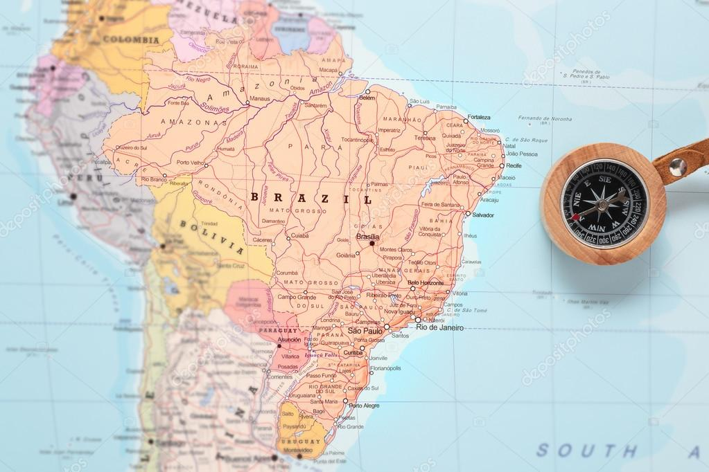 compass on a map pointing at brazil and planning a travel destination photo by mattiaath