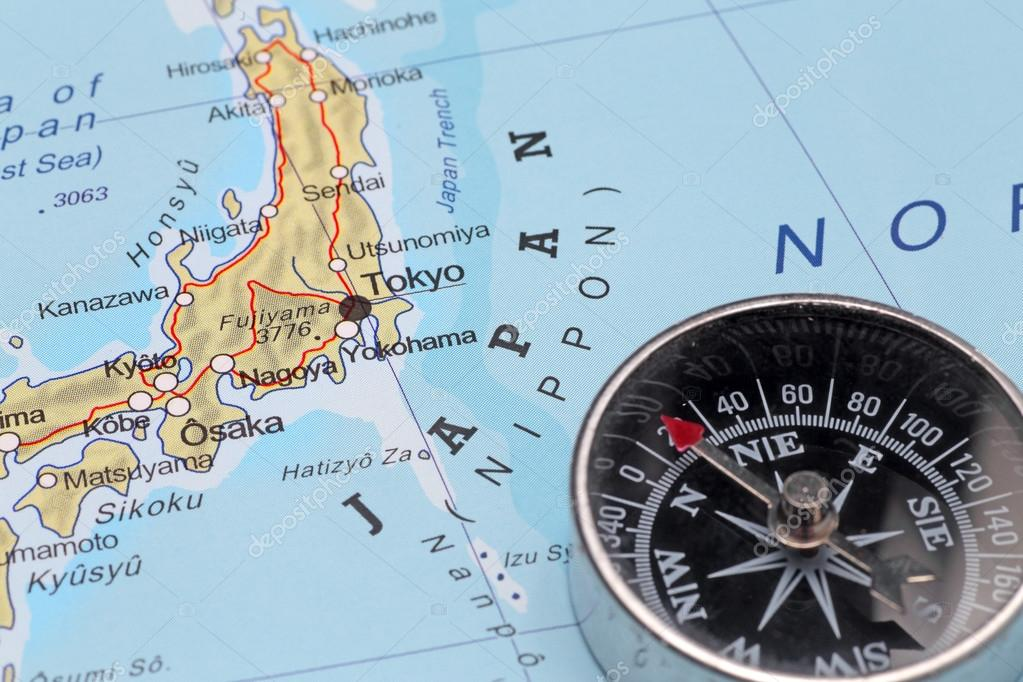 compass on a map pointing at japan and planning a travel with destination tokyo photo by mattiaath