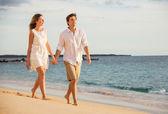 romantický šťastný pár, chůze po pláži při západu slunce. usmíval se, holdin