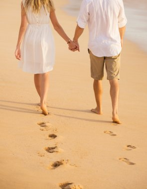 Romantic couple holding hands walking on beach at sunset. Man an