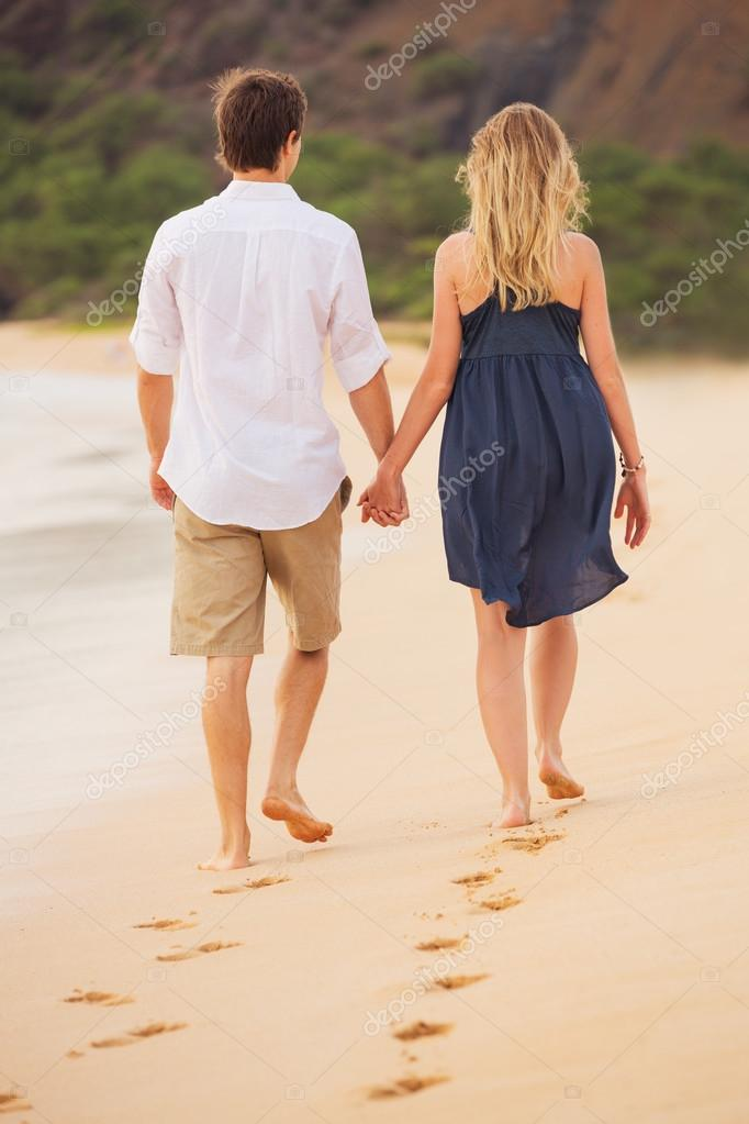 Romantic happy couple walking on beach at sunset. Smiling holdin