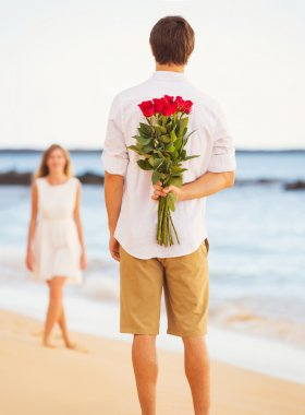 Romantic Young Couple in Love, Man holding surprise bouquet of r