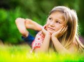 Ritratto di una bambina sorridente, sdraiato sullerba verde
