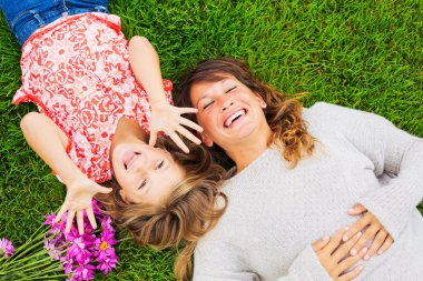 Happy mother and daughter relaxing outside on green grass. Spending quality time together, Real emotions stock vector