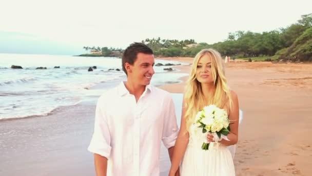újonnan házas pár trópusi tengerparton naplementekor
