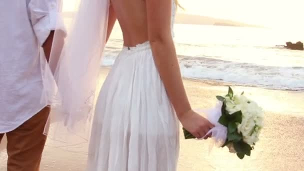 Newly married couple on tropical beach at sunset