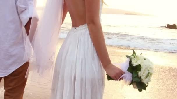 novomanželé na tropické pláži při západu slunce