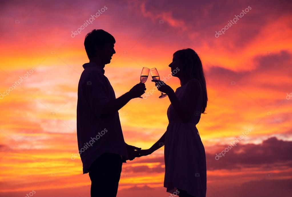 Silhouette of couple drinking champagne at sunset