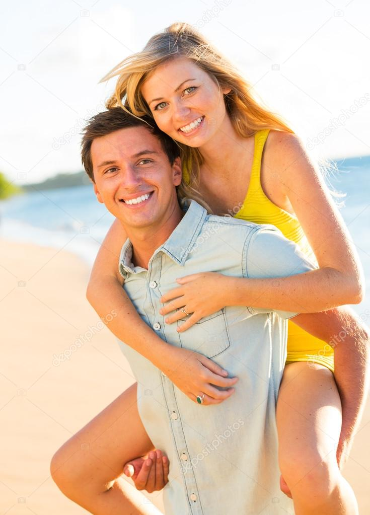 Attractive Couple Playing on the beach at Sunset