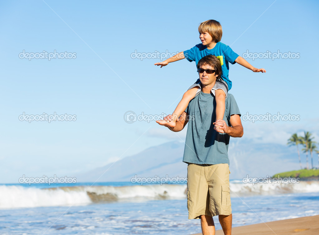 Happy father and son playing on tropical beach, carefree happy f