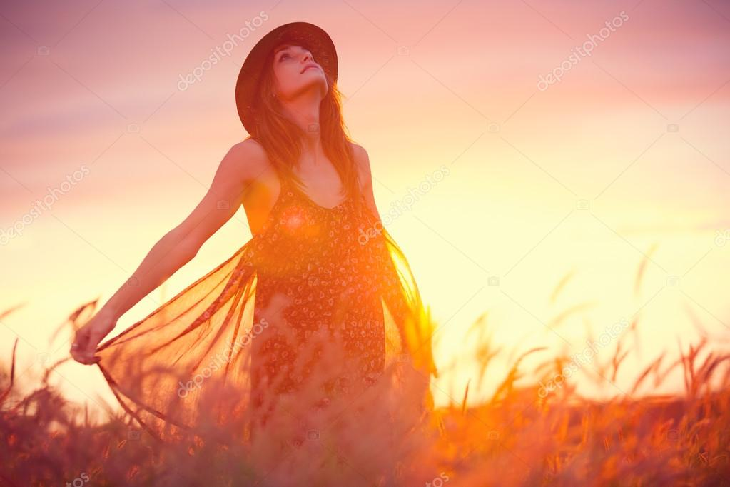 Woman in golden field at sunset