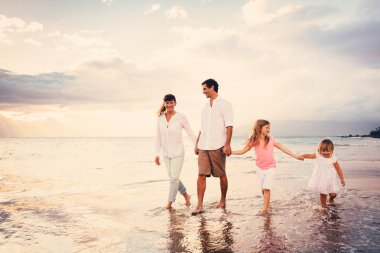 Happy Young Family have Fun Walking on Beach at Sunset
