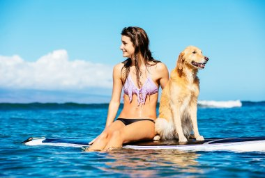 Young Woman Surfing with Her Dog