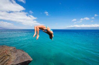 Woman doing backflip into ocean