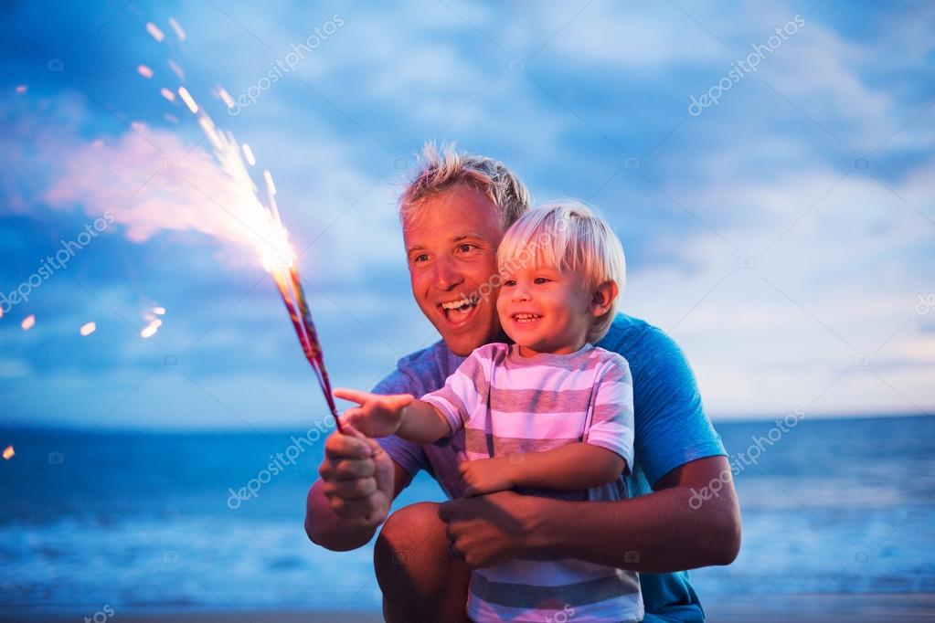 Father and son lighting fireworks