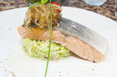 Fotografie Baked salmon with vegetables on a white background in the restaurant
