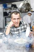 Šéfkuchař připravuje jídlo v kuchyni