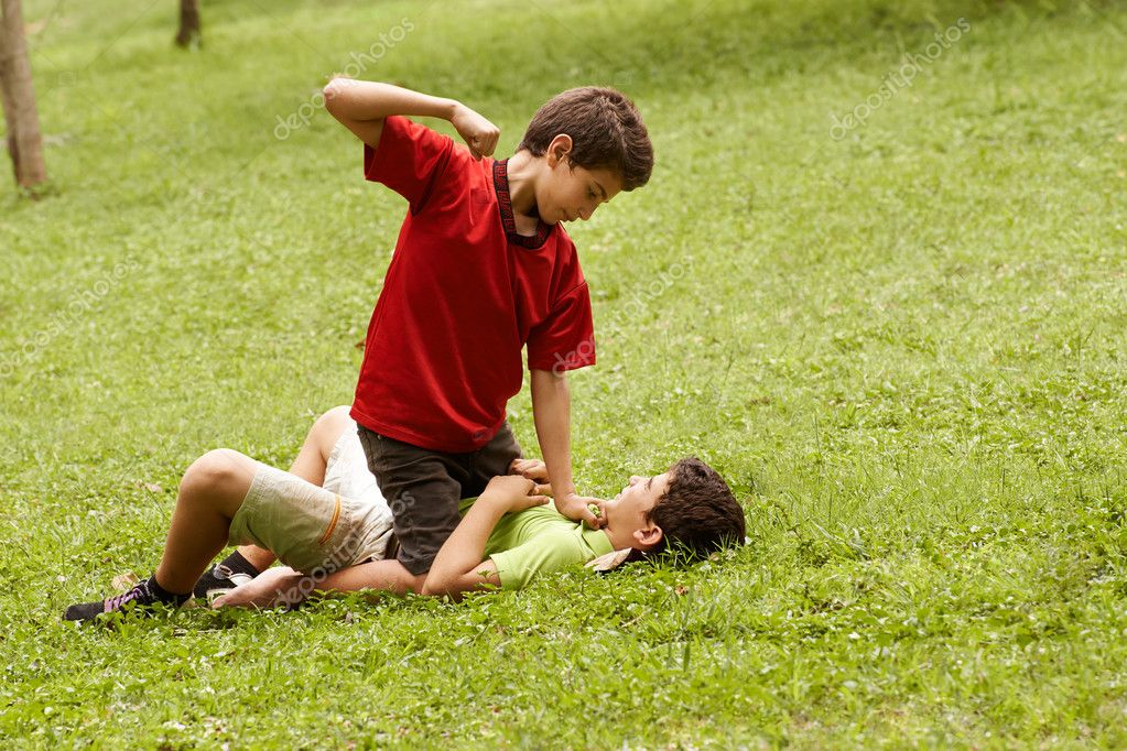 Violent Kid Fighting And Hitting Scared Boy In Park Stock Photo Two Young