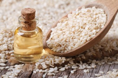 Fresh sesame oil in a glass bottle and seeds in a wooden spoon